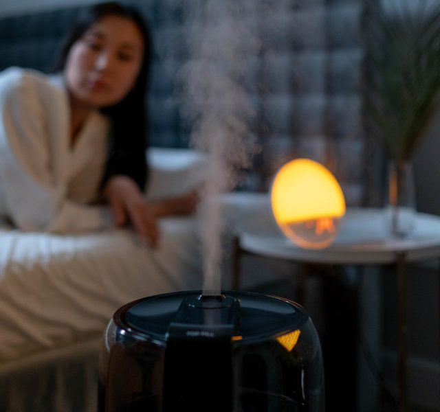 Woman on Bed Looking at Humidifier