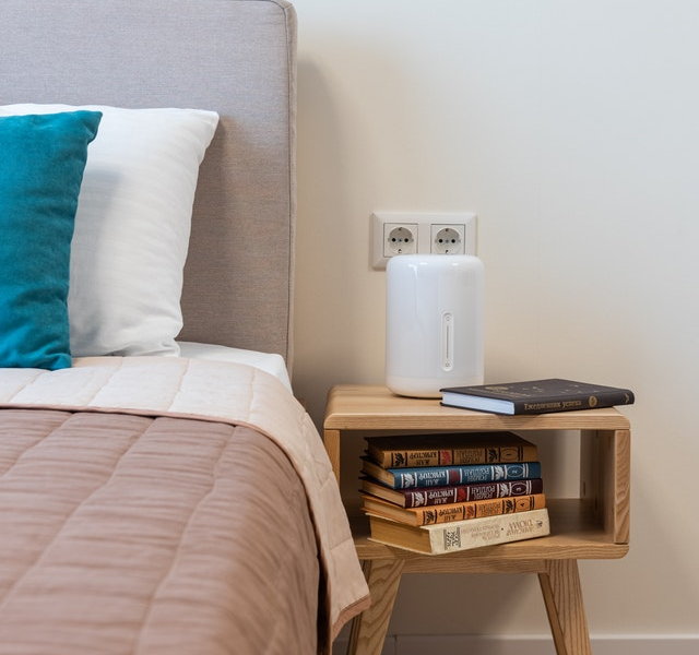 White Humidifier on Top of Bedside Table with Books